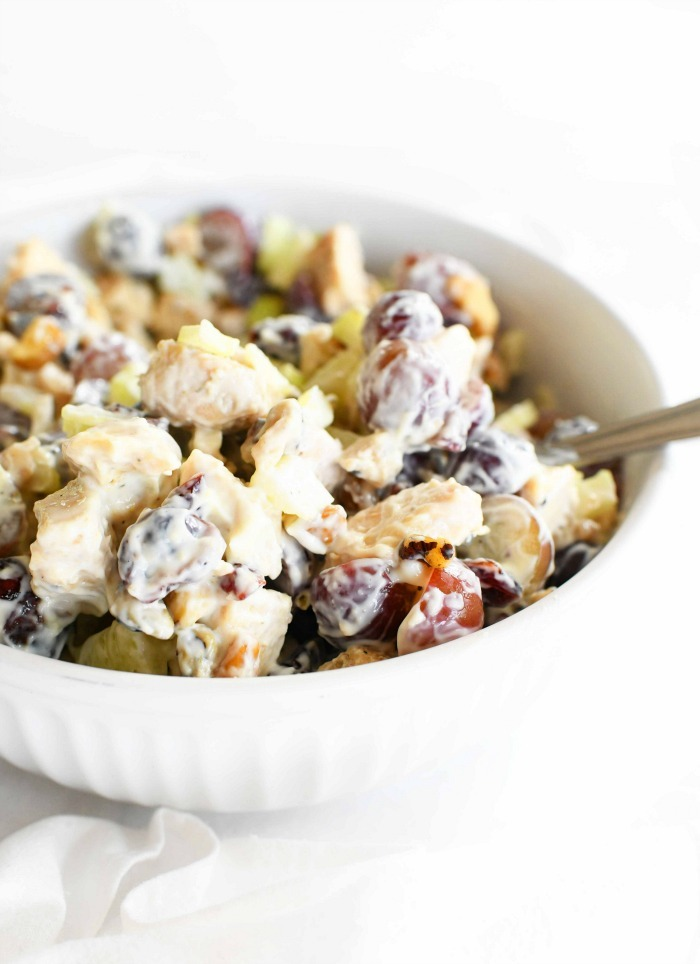 Chicken with Grapes salad in a white dish with a spoon.