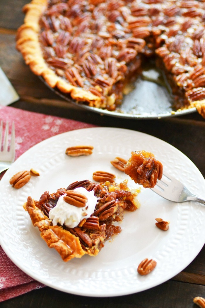 Pecan Pie slice on white dish on wooden table.