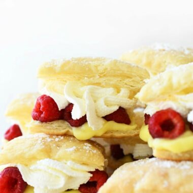 Raspberry Lemon Cream Puffs stacked on each other on a white tray.