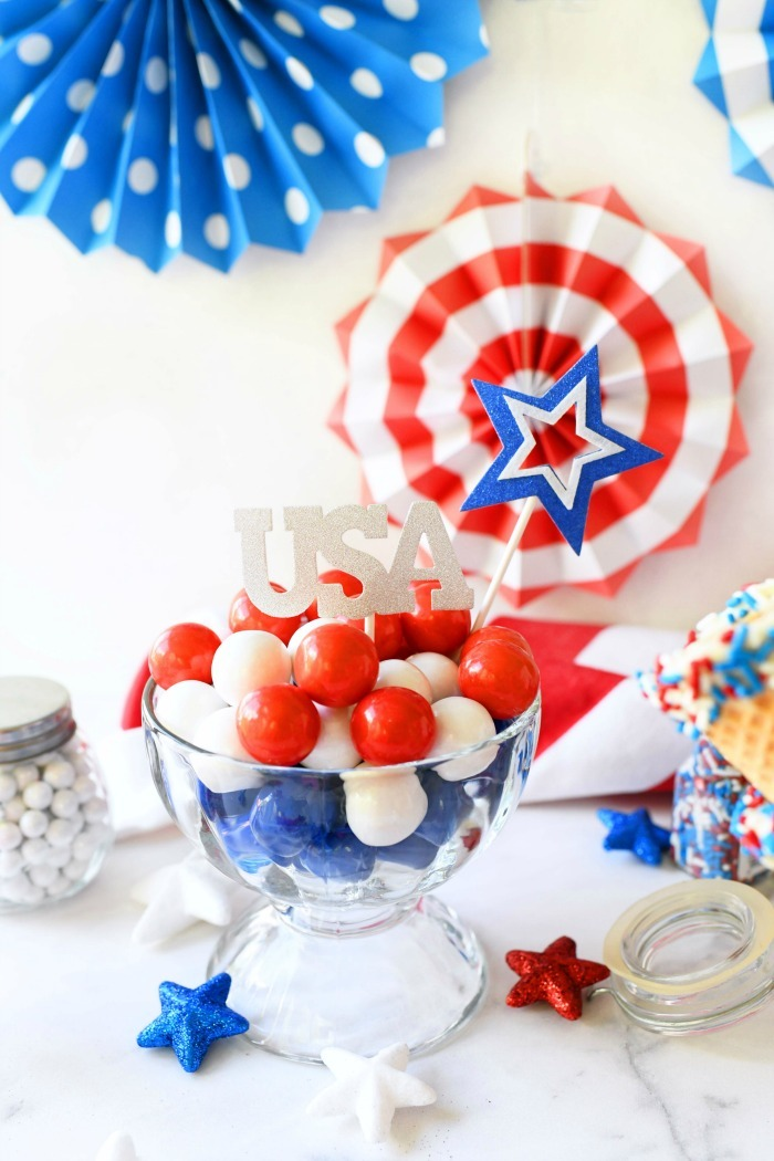 Red white blue gumballs in a glass dish.