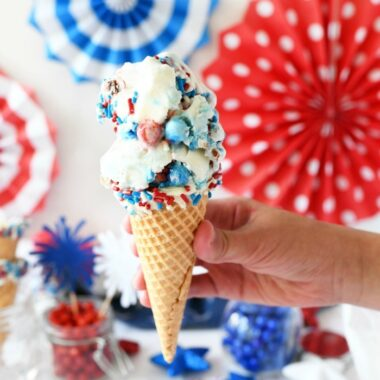 Sixlets ice cream cone in hand with patriotic decor in the background.