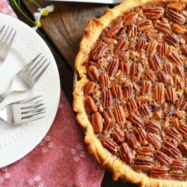 Southern Style Pecan Pie on a table with a pink napkin and plates.