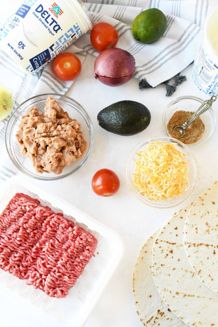 Beef chimichanga recipe ingredients on white table.