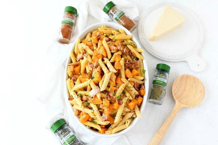 Butternut Pasta recipe in oval dish with wooden spoon and spices.