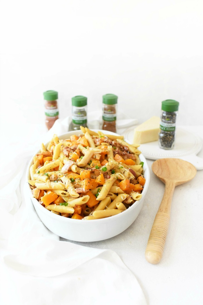 Butternut Squash Pasta with onion on table in white casserole dish.