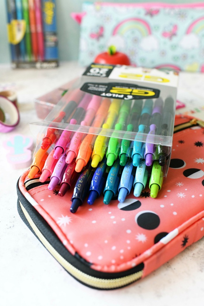 Colorful Pilot G-2 Pens on peach pen case.
