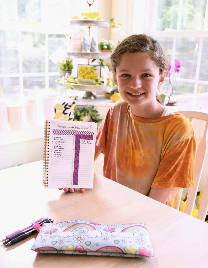 Girl with bullet journal smiling.