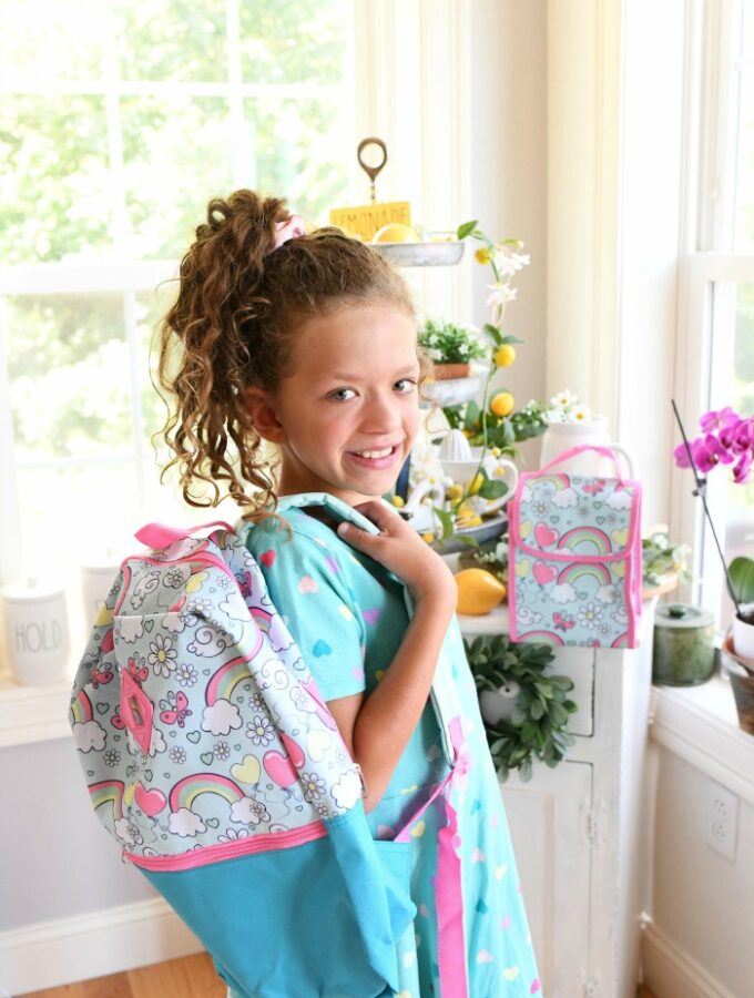 Girl with colorful backpack smiling.