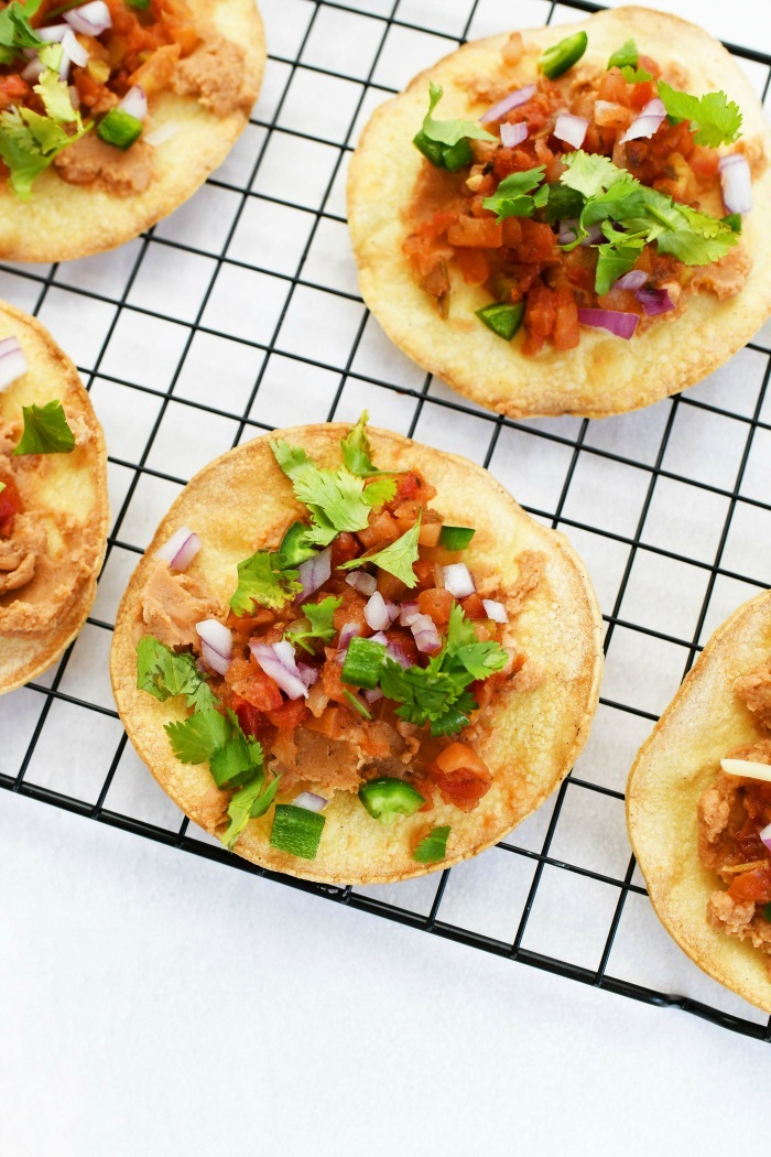 Oven baked tostadas on a black wire rack.