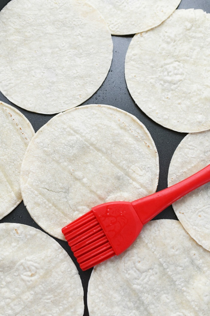 Oven baked tostadas with a red pastry brush.