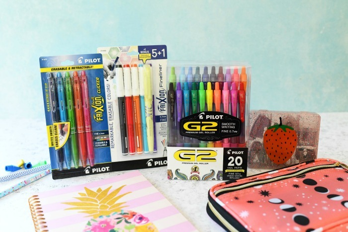 Pilot pen products with school supplies on blue and white table.