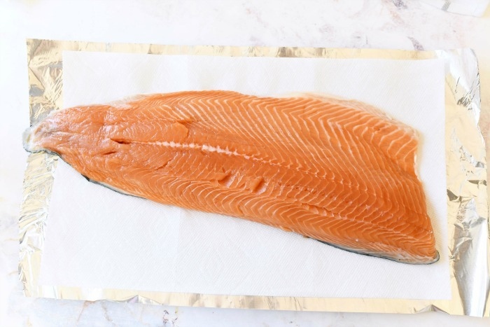 Salmon filet raw on foil.