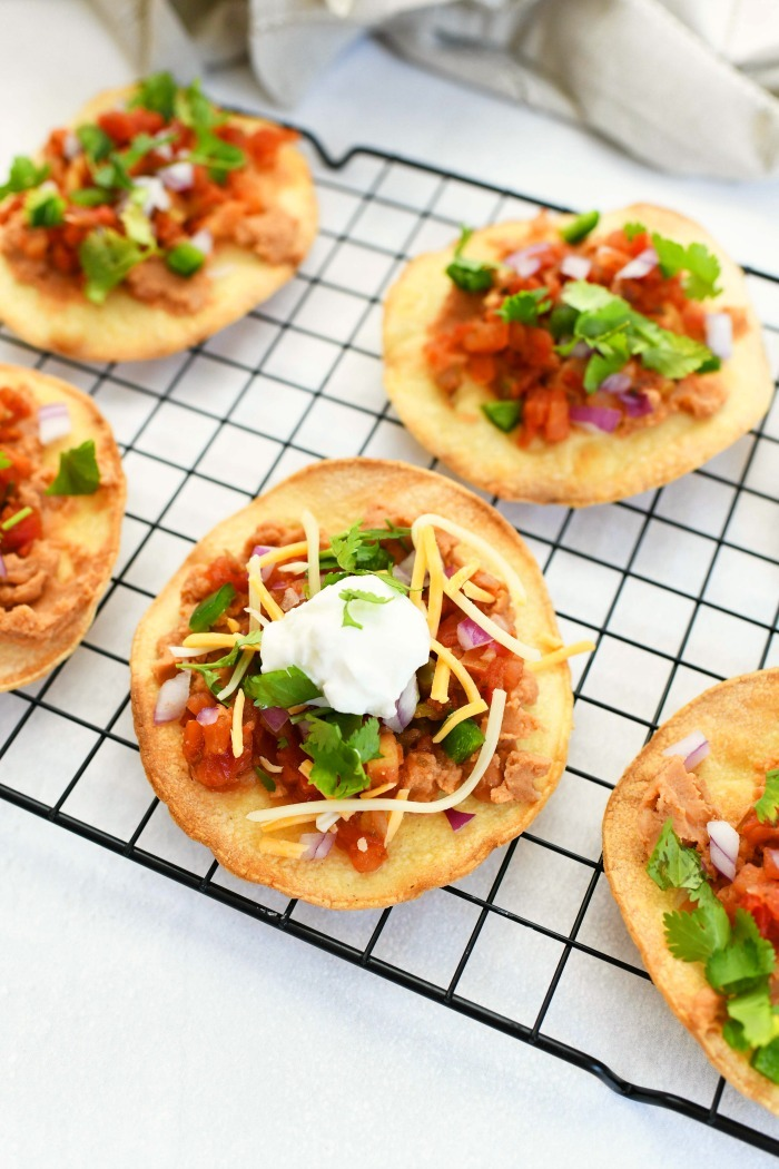 Tostadas on a wire rack with fresh topppings.