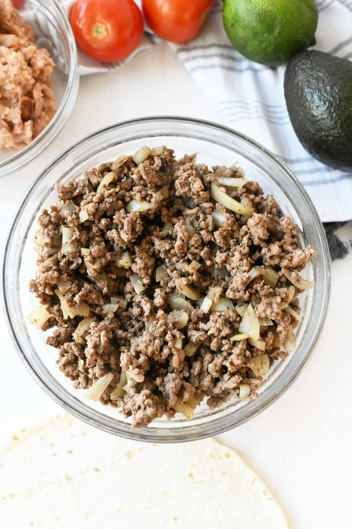 ground beef and onion in glass bowl.