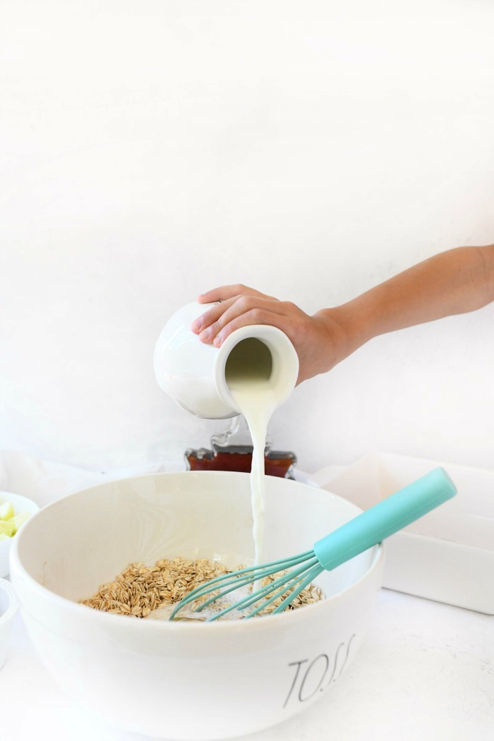 milk pouring from a white glass into mixing bowl.