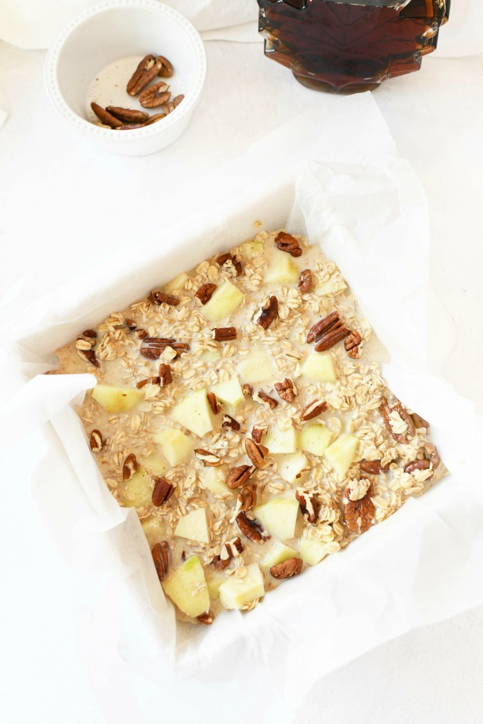 Baked oatmeal with apples prebaked in a white lined dish.