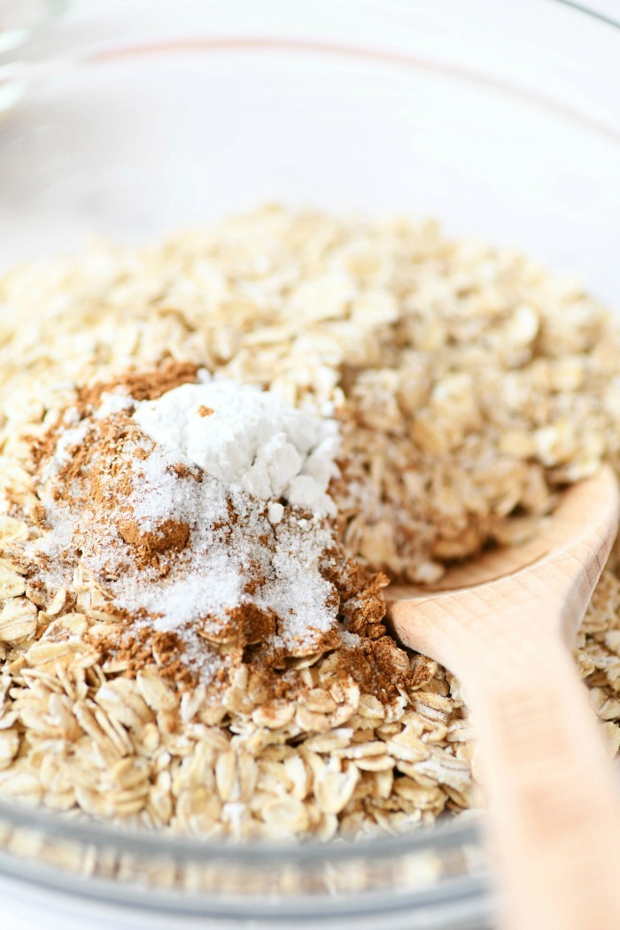 Baking powder and oats in a glass bowl with a wooden spoon.
