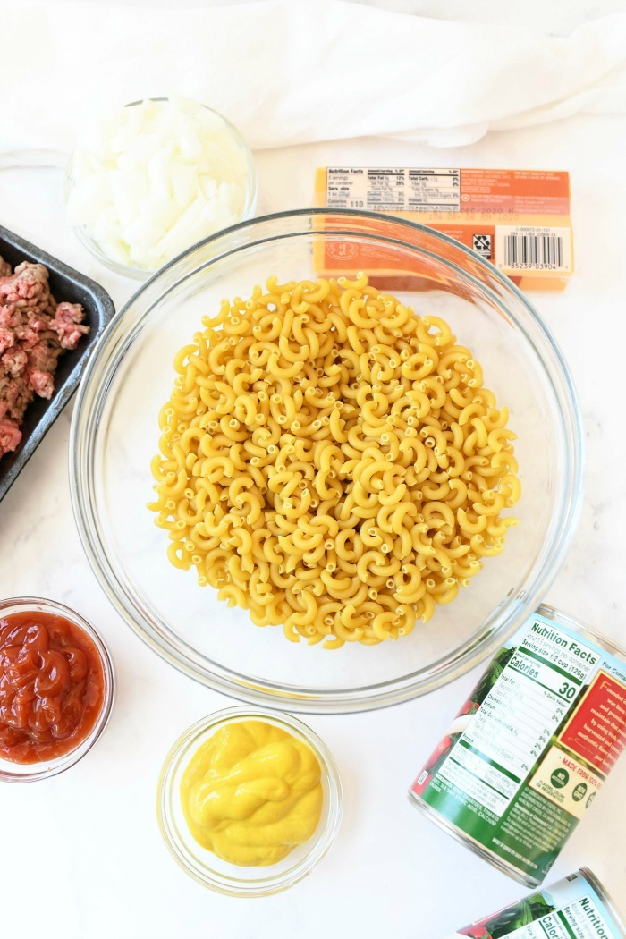 Cheeseburger pasta ingredients on a white table.