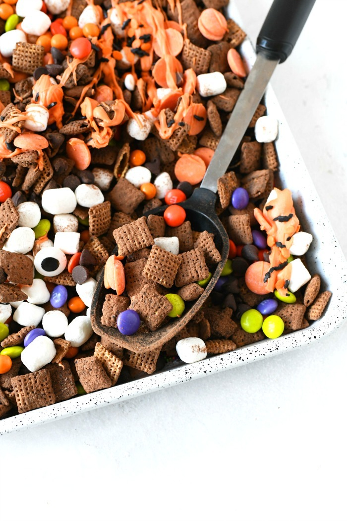 Halloween Chex mix on a baking sheet with a spoon up close.