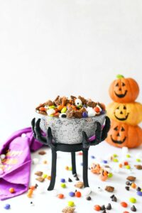 Halloween Muddy Buddys on a white table with pumpkins and candy.