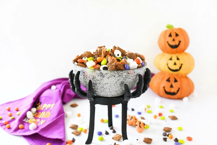 Halloween snack mix in a creepy glass bowl with pumpkins in the background.