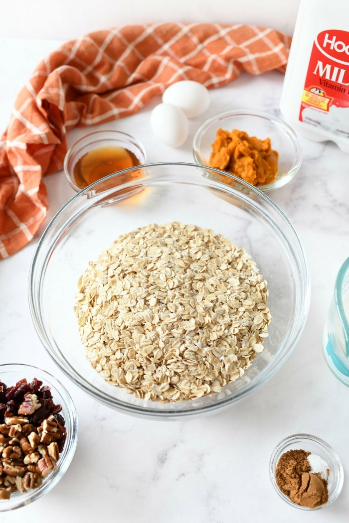 Old fashioned oats in a bowl near ingredients.