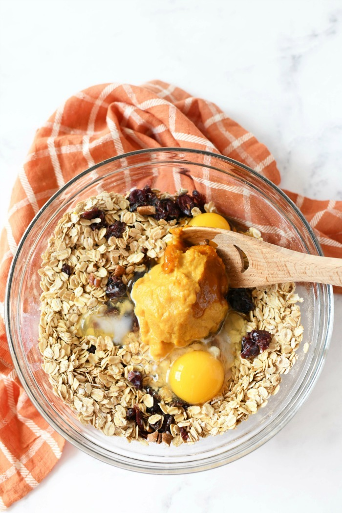 Pumpkin cranberry oat muffins with a wooden spoon in a bowl.