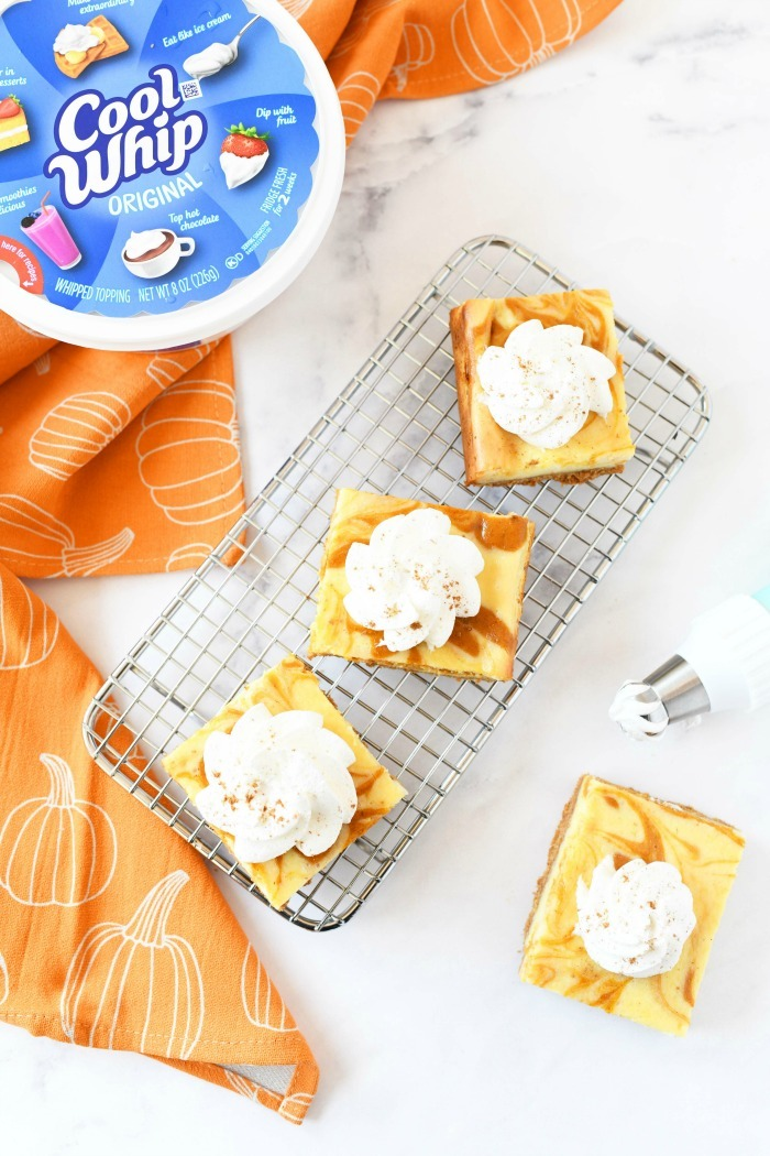Whipped cream pumpkin bars on  baking rack with a Cool Whip package.