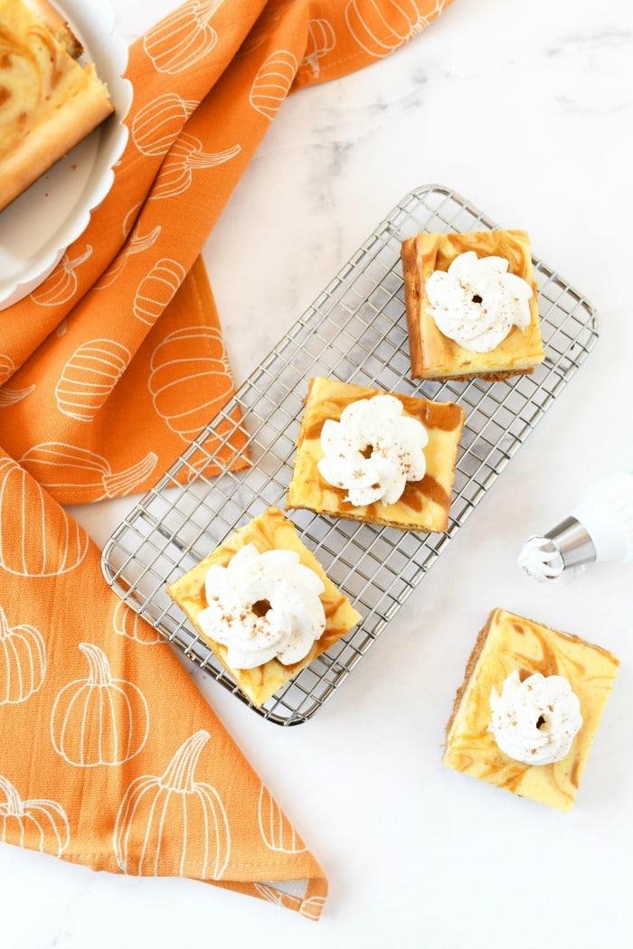 whipped cream on pumpkin cheesecake with a pumpkin napkin.