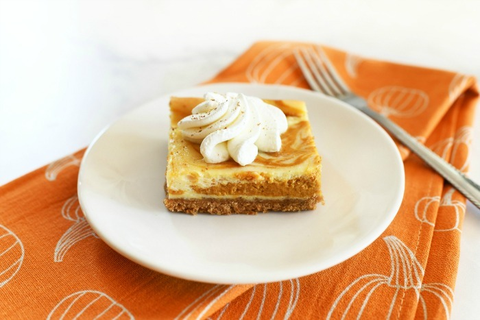 Pumpkin cheesecake bar with a white plate and fork.