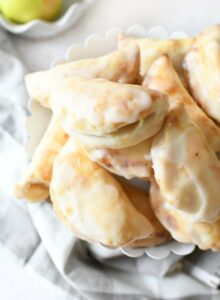 Apple Hand Pies on a white stand with a gray napkin.
