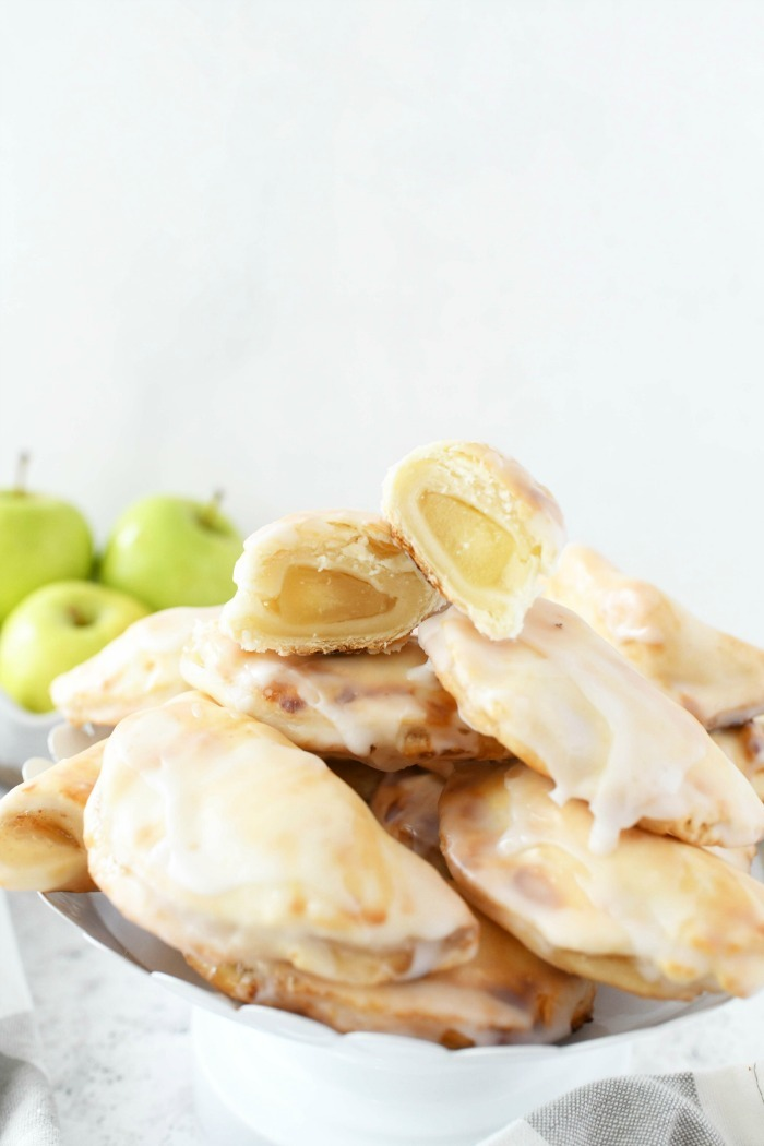 Apple mini hand pies on a white baking stand with green apples in the background.