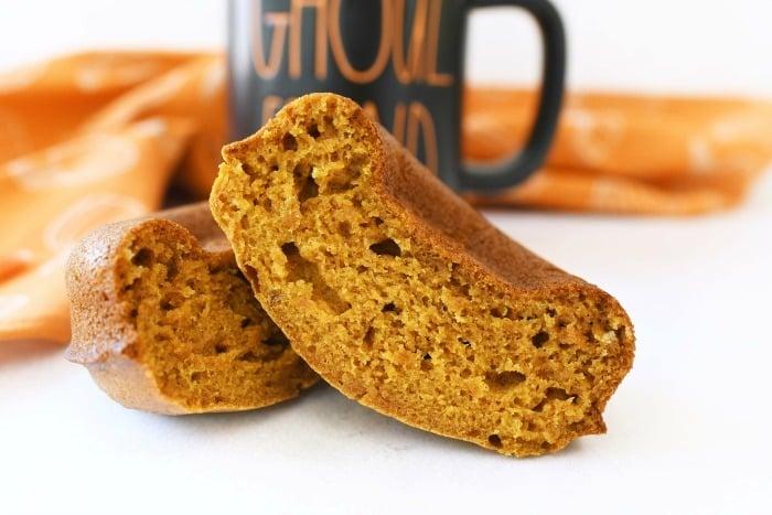 Baked Pumpkin Donuts Recipe in half near a halloween mug.