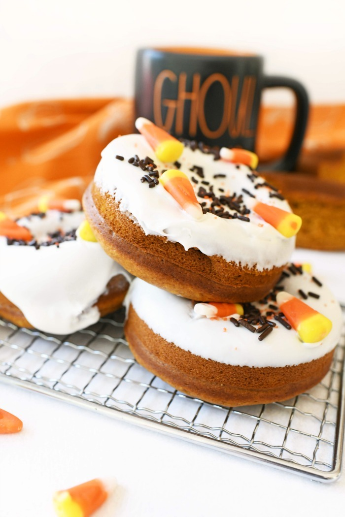 Baked pumpkin donuts stacked on a wire rack with a mug and orange napkin nearby.