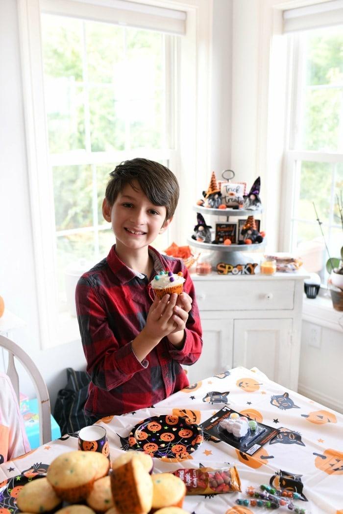 Boy with Halloween cupcake.