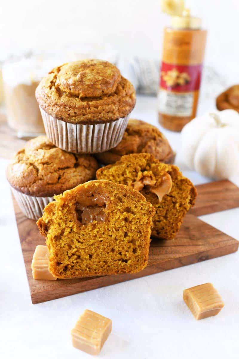 Caramel stuffed pumpkin muffins on a mini wood board.