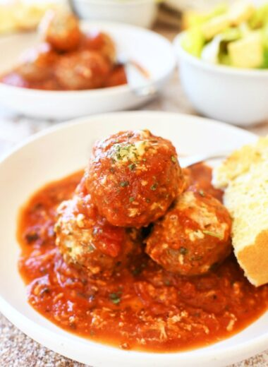 Cheesy meatballs casserole in a white dish with cheese and bread.