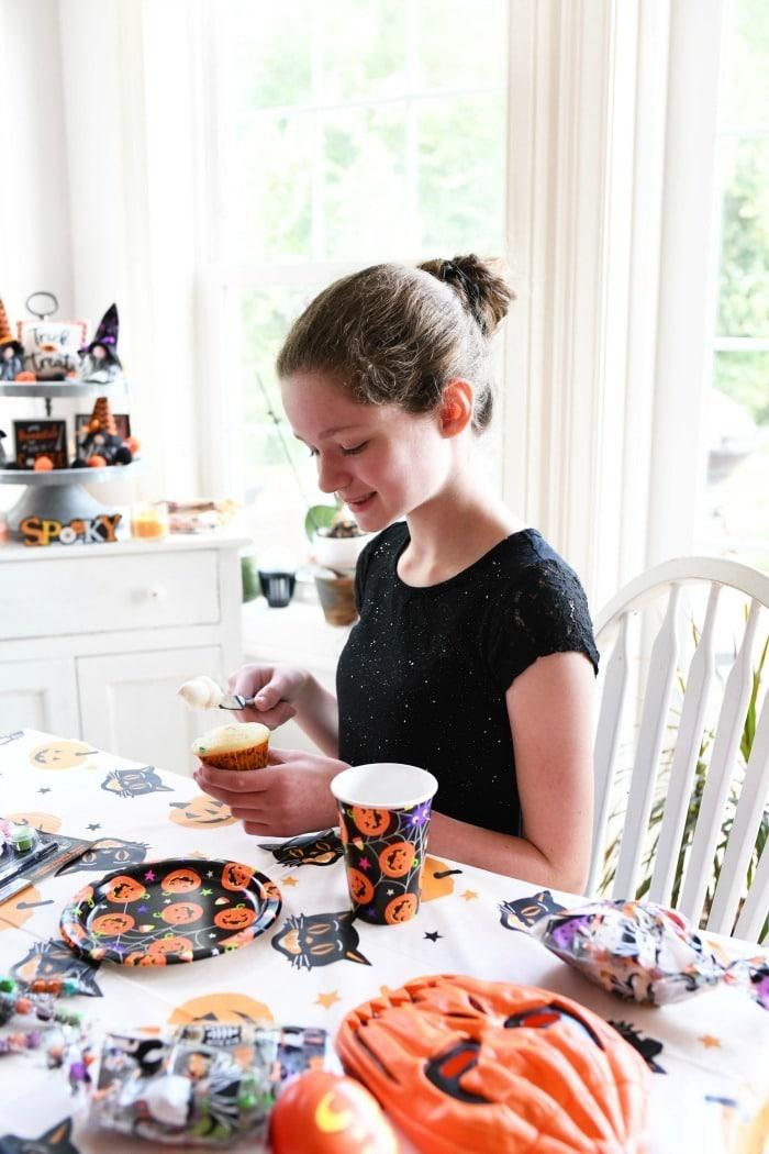Girl decorating Halloween Cupcakes.