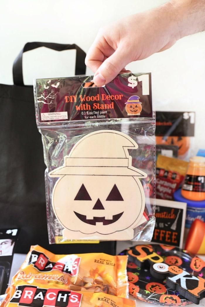Halloween wooden pumpkin craft in a hand.