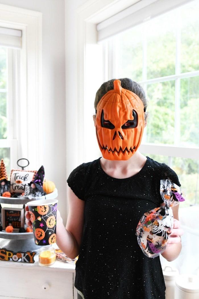 Girl in a Halloween pumpkin mask