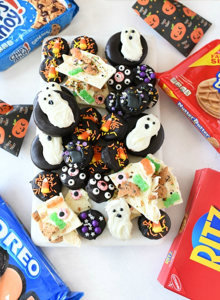 Halloween semi-homemade snacks on a white tray with cookie boxes around the tray.