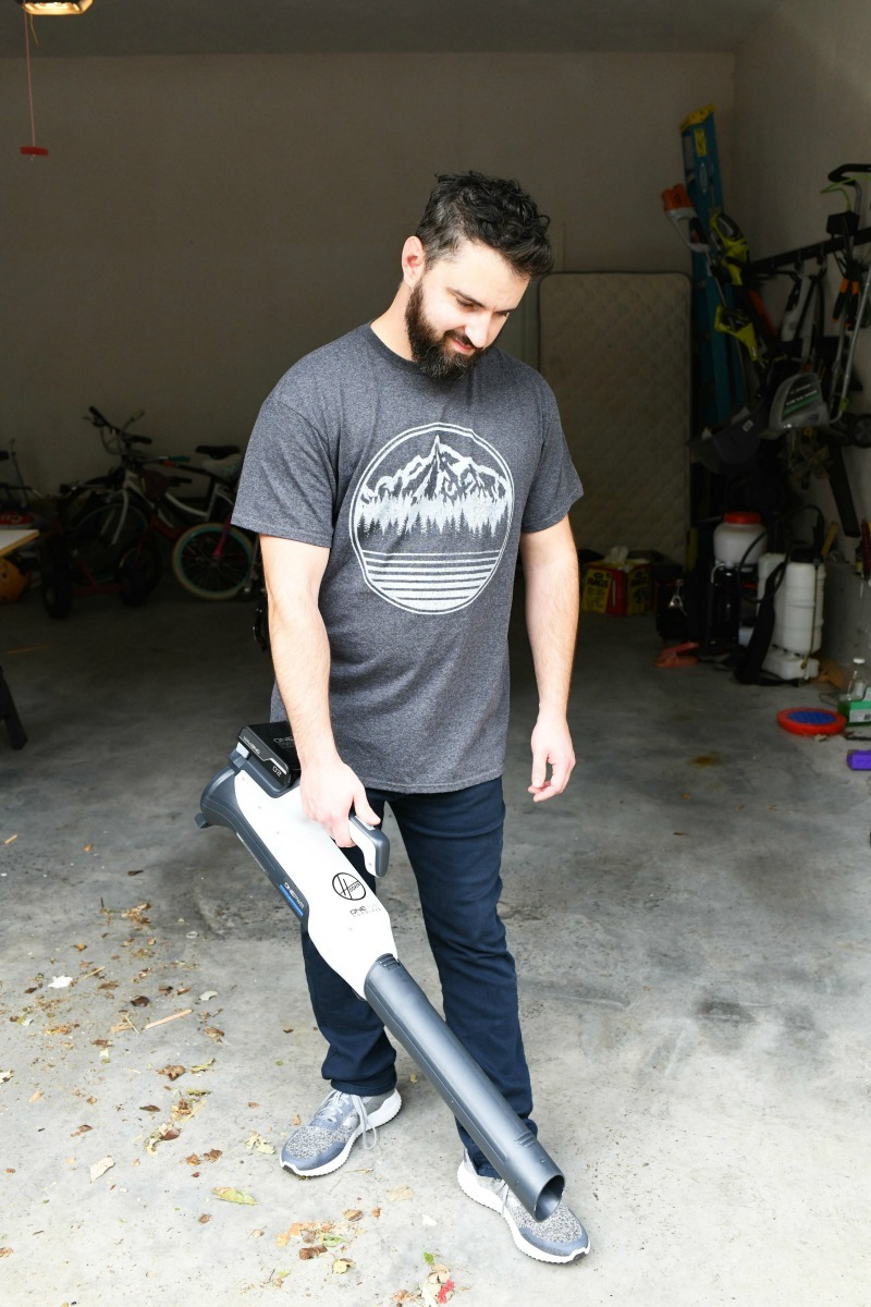 man using a Hoover Floor Sweeper in the garage.