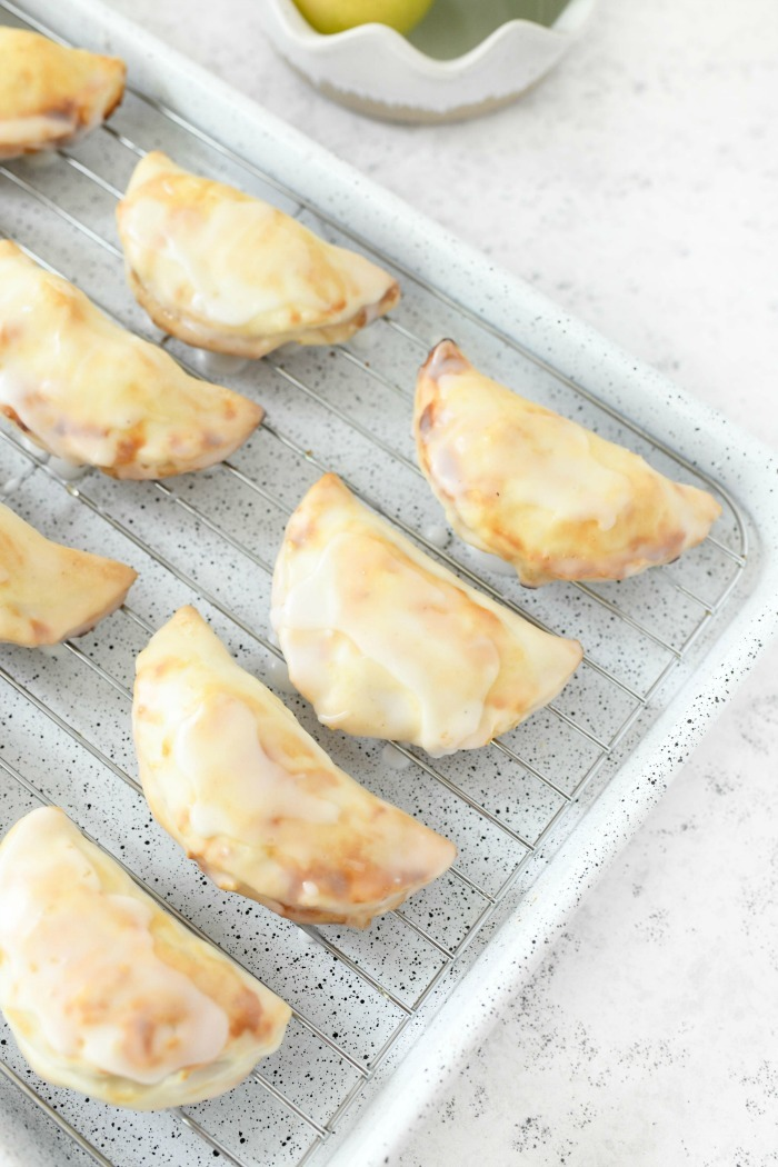 Iced Apple Hand Pies on a white baking tray.