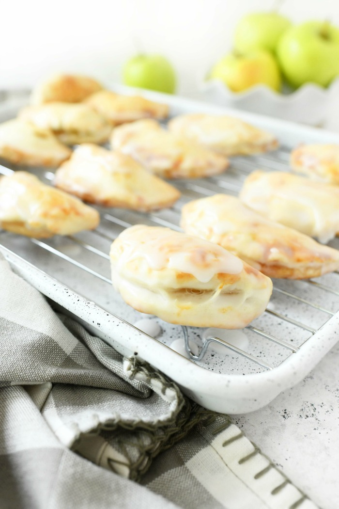 Iced Apple Pies on a white baking rack with a grey checkered napkin.