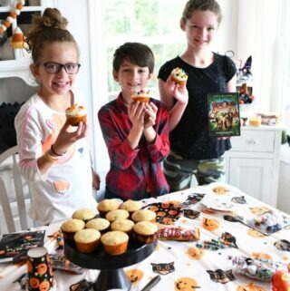 Kids decorating Halloween Cupcakes at a Halloween party.