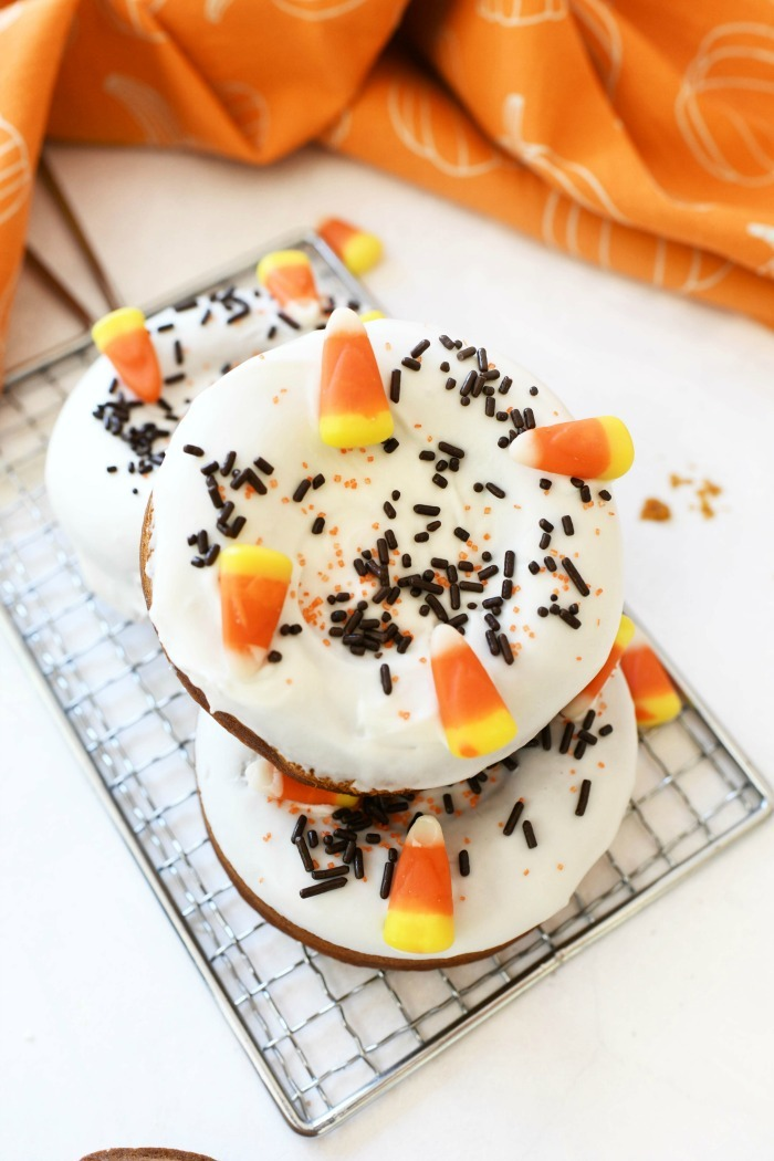 Pumpkin Cake Donuts decorated with candy corns on a wire rack with an orange napkin.