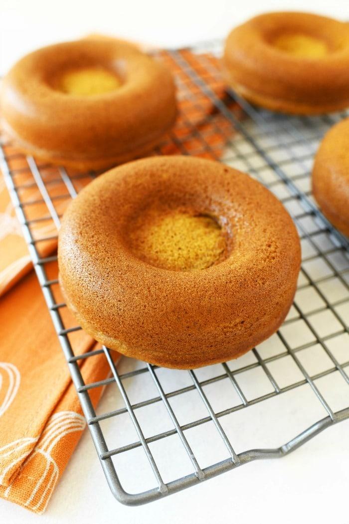 Pumpkin baked doughnuts on a cooling rack.