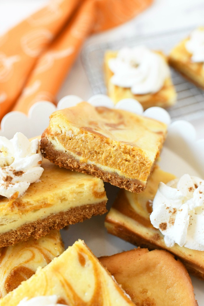Pumpkin cheese bars on a white cake stand.