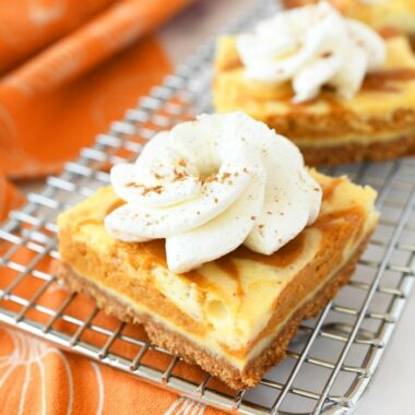 Pumpkin cheesecake with whipped topping on a baking rack with an orange napkin.