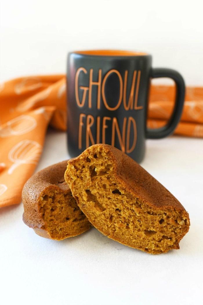 Soft Pumpkin cake donuts near a Rae Dun Halloween mug.